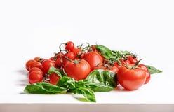 Fondo italiano dell'alimento con l'olio d'oliva del basilico dei pomodori e gli interi spaghetti del grano Fotografie Stock Libere da Diritti