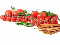 Fondo italiano dell'alimento con l'olio d'oliva del basilico dei pomodori e gli interi spaghetti del grano Fotografia Stock Libera da Diritti