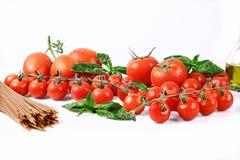Fondo italiano dell'alimento con l'olio d'oliva del basilico dei pomodori e gli interi spaghetti del grano Fotografia Stock