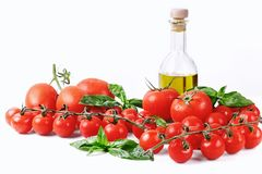 Fondo italiano dell'alimento con l'olio d'oliva del basilico dei pomodori e gli interi spaghetti del grano Immagine Stock