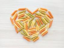 Fondo italiano texturizado de la comida - forma cruda colorida del corazón de las pastas del penne en la tabla de madera fotos de archivo