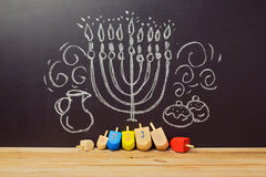 Fondo judío creativo de Jánuca del día de fiesta con el dreidel del top de giro sobre la pizarra con el dibujo de la mano