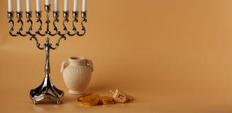 Fondo judío de Jánuca del día de fiesta con el menorah, el top de giro, las monedas y el jarro fotografía de archivo