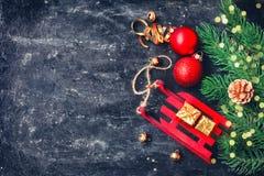 Fondo lamentable del negro de la Navidad del día de fiesta, juguete rojo del trineo, bolas, Foto de archivo libre de regalías