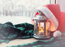 Fondo-linterna del invierno de la Navidad y del Año Nuevo con la vela y sombrero de Papá Noel en la naturaleza del alféizar y del Fotografía de archivo