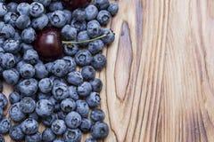 Fondo luminoso naturale dei mirtilli e delle ciliege maturi freschi naturali su una tavola di legno spazzolata Immagini Stock Libere da Diritti