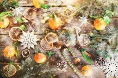 Fondo mágico de la Navidad - madera del vintage, bastón de caramelo, casa, canela, anís de estrella, mandarines dulces con las ho Foto de archivo libre de regalías