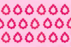 Fondo médico de los períodos de las mujeres Píldoras rojas bajo la forma de gotas de la sangre en un fondo rosado fotos de archivo