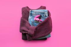 Fondo mínimo femenino moderno del otoño del invierno con el suéter acogedor de Borgoña, tejanos, flores rosadas fotos de archivo