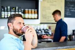 Fondo móvil del barista del café de la conversación del hombre Café de la bebida mientras que espera Café de la orden del smartph imagenes de archivo