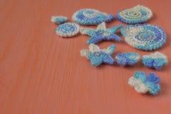 Fondo marino con los elementos del arte del ganchillo del cordón del algodón: las estrellas, cáscaras, flores hechas suavemente d Imagen de archivo