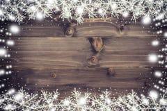 Fondo marrone di natale e bianco come la neve di legno con i fiocchi di neve Immagini Stock