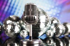 Fondo, micrófono y bolas de discoteca de la música Fotos de archivo