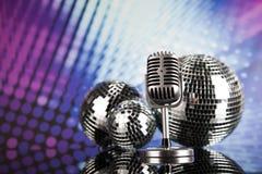 Fondo, micrófono y bolas de discoteca de la música Imagen de archivo libre de regalías