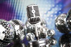 Fondo, micrófono y bolas de discoteca de la música Imagen de archivo