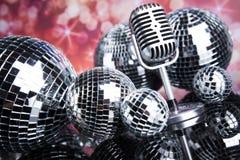 Fondo, micrófono y bolas de discoteca de la música Fotografía de archivo libre de regalías