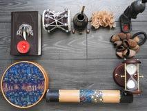 Fondo mistico con un vecchio libro, le candele ed altri attributi Halloween ed il concetto occulto del rituale di magia nera immagine stock libera da diritti