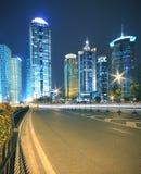 Fondo moderno del edificio de oficinas de la noche del coche con los rastros ligeros Imagen de archivo