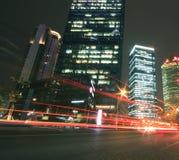 Fondo moderno del edificio de oficinas de la noche del coche con los rastros ligeros Imagenes de archivo
