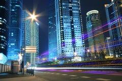 Fondo moderno dell'edificio per uffici della notte dell'automobile con le tracce leggere Fotografia Stock