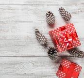 Fondo moderno, tarjeta de Navidad, fondo blanco con los regalos rodeados por los conos negros, regalos hechos a mano en un estilo Foto de archivo libre de regalías