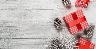 Fondo moderno, tarjeta de Navidad, en el fondo blanco con los regalos rodeados por los conos de abeto, regalos hechos a mano en u Imagen de archivo libre de regalías