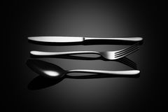 Fondo negro de la comida con el cuchillo, la bifurcación y la cuchara Foto de archivo