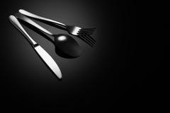 Fondo negro de la comida con el cuchillo, la bifurcación y la cuchara Imagen de archivo
