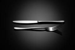 Fondo negro de la comida con el cuchillo y la bifurcación Imagen de archivo libre de regalías