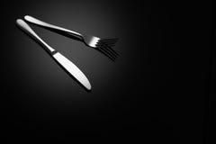 Fondo negro de la comida con el cuchillo y la bifurcación Foto de archivo libre de regalías