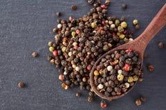 Fondo negro de la comida con las especias Una mezcla de pimientas con una cuchara de madera en una piedra de la pizarra Imagen de archivo libre de regalías