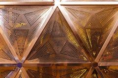 Fondo negro de la malla del altavoz del metal agrupe el treugolnikov con los agujeros perforados de diverso diámetro como rojo br Imágenes de archivo libres de regalías