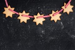 Fondo negro de la Navidad con las galletas Foto de archivo libre de regalías