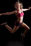Fondo negro de salto alegre de la muchacha del deporte Fotografía de archivo