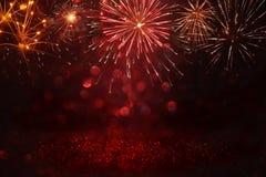 Fondo nero e rosso astratto dell'oro, di scintillio con i fuochi d'artificio notte di Natale, quarta del concetto di festa di lug Fotografie Stock