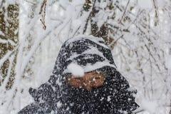 Fondo, nieve de una rama de árbol derramada en una cabeza del ` s del hombre en una chaqueta negra caliente Fotografía de archivo