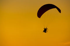 Fondo nuvoloso della luce arancio di tramonto della siluetta di Paramotor fotografia stock