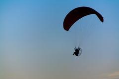 Fondo nuvoloso leggero blu-chiaro di tramonto della siluetta di Paramotor immagini stock libere da diritti