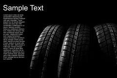 Fondo oscuro con los neumáticos del invierno Imagenes de archivo
