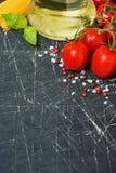 Fondo oscuro con los tomates de cereza, las pastas y el aceite de oliva frescos Foto de archivo