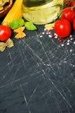 Fondo oscuro con los tomates de cereza, pastas, albahaca fresca Imagen de archivo libre de regalías