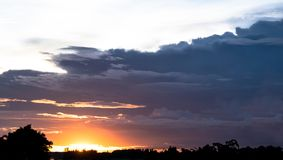 Fondo oscuro de cielo nublado sobre la puesta del sol en el cielo de la tarde en el campo de Tailandia foto de archivo libre de regalías