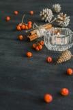 Fondo oscuro de la Navidad con las velas y las bayas de la ceniza de montaña Conos del pino blanco Ramifican las bellotas Foto de archivo libre de regalías