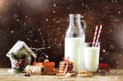 Fondo oscuro de la Navidad con la nieve y el bokeh, espacio de la copia Botella, vidrio con la leche para Papá Noel, galletas, cu Foto de archivo