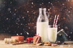 Fondo oscuro de la Navidad con la nieve y el bokeh, espacio de la copia Botella, vidrio con la leche para Papá Noel, galletas, cu Imagen de archivo