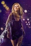 Fondo púrpura y agua de la muchacha hermosa Fotografía de archivo