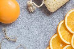 Fondo para bañar tema: el jabón anaranjado, las rebanadas de naranja y la esponja del baño en la toalla de baño Foto de archivo