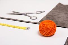 Fondo para el hilo anaranjado del sastre y las herramientas de costura Foto de archivo