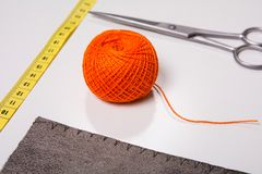 Fondo para el hilo anaranjado del sastre y las herramientas de costura Imagen de archivo