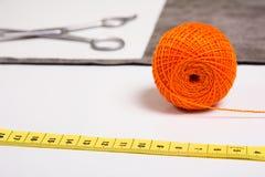 Fondo para el hilo anaranjado del sastre y las herramientas de costura Foto de archivo libre de regalías